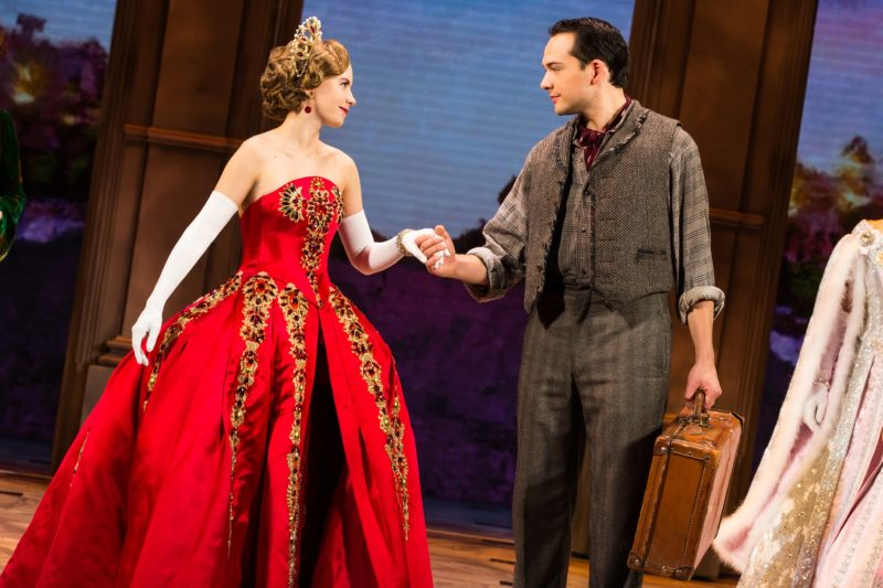 Anastasia, dressed in her royal red ball gown, takes Dimitry's hand.