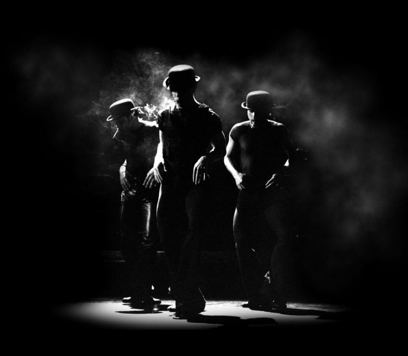 Three dancers in the company of CHICAGO on Broadway are backlit in a pool of light wearing bowlers and smoking cigarettes.